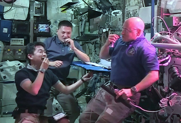 L-R: Japan Aerospace Exploration Agency astronaut Kimiya Yui, with Nasa astronauts Kjell Lindgren and Scott Kelly eat red romaine lettuce grown on board the International Space Station. (AFP  / Handout / Nasa TV)
