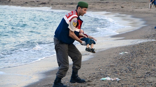 A Turkish police officer carries a young boy who drowned in a failed attempt to sail to the Greek island of Kos. (Pictures: Reuters)