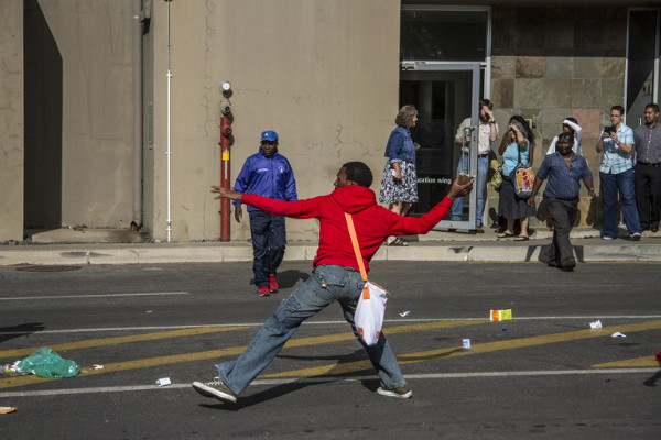 A student prepares to hurl a stone as students and janitors scuffle with Wits university security personnel during a protest against the outsourcing of services at the campuses in Johannesburg on October 28, 2015. AFP / Zinyange Auntony