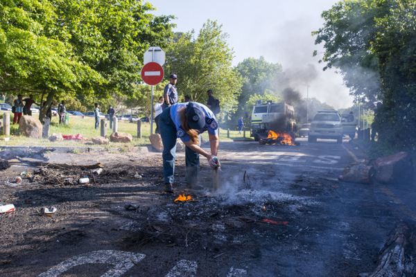 Putting out fires, a traffic official helps  extinguish a burning barricade at an exit on UCT upper campus on October 20 2015. Photo by David Harrison