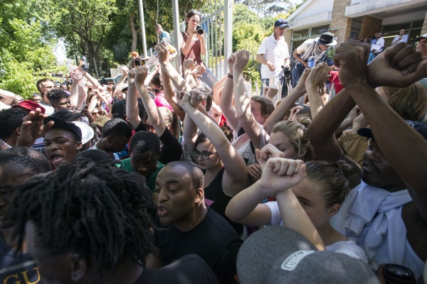 White UCT protesters form a human shield around black protesters to protect them from the police outside the Rondebosch police station, 20 October 2015. Photo by David Harrison