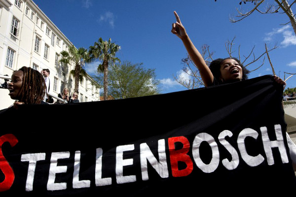 "Students hold a banner reading ""Stellenbosch"" during a protest against allegations of racism on campus brought to light by a documentary called Luister (""Listen"" in Afrikaans) on September 1, 2015, in Stellenbosch. The protest was organised by the Open Stellenbosch organisation.  (AFP  / Rodger Bosch)"