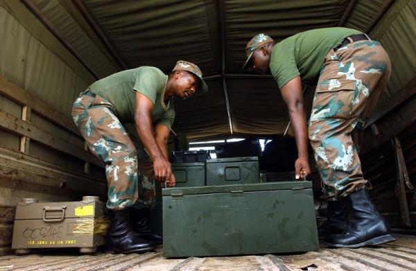 SANDF members load boxes of ammunitions on an army truck waiting on the airport tarmac April 27 2003, in Bujumbura, Burundi. (AFP / Marco Longari)