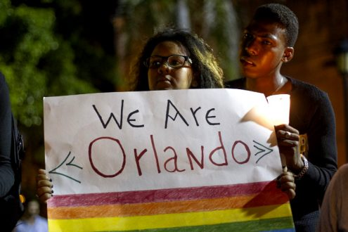 A woman holds up a sign and listens to speakers at a memorial gathering for those killed in Orlando at the Colonial Zone in Santo Domingo on June 14, 2016. (Erika Santelices/AFP)