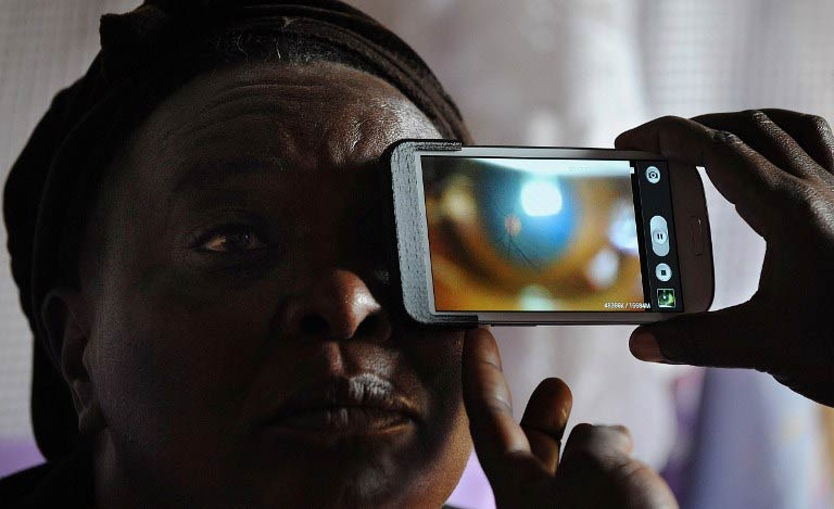 A technician scans the eye of Mary Wambui at her home with a smartphone application as she takes part in an ophthalmological study and examination. (Pic: AFP)