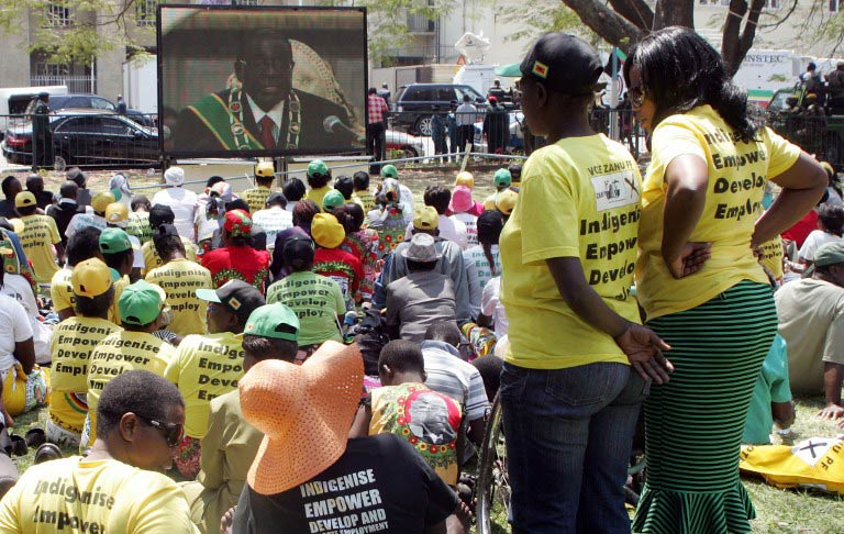 Supporters of Zimbabwe's President Robert Mugabe listen to his televised speech during the official opening ceremony of the first session of Zimbabwe's Parliament in Harare on September 17 2013. (Pic: AFP)