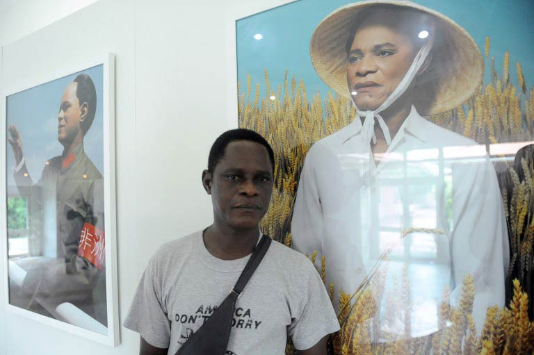 Samuel Fosso poses next to a series of self-portraits in which he is dressed as the former Communist Party chairman Mao Zedong. (Pic: AFP)