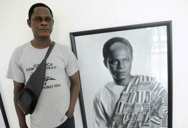 Samuel Fosso poses next to a self-portrait, which sees him dressed as former Ghanaian leader Kwame Nkrumah. (Pic: AFP)