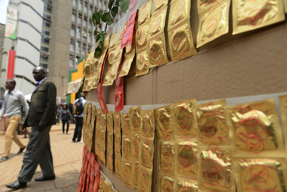 Kenyans walk past condoms exhibited in the streets as workers distribute them on February 14 2014 to promote safe sex practices during the Valentine week and to mark International Condom Day. (Pic: AFP)