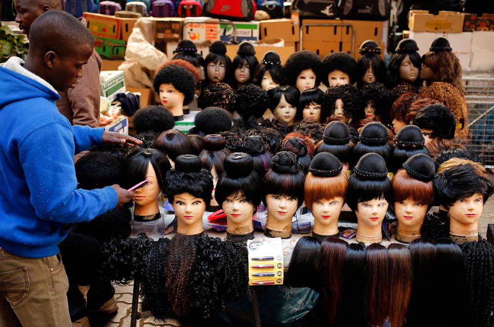 A man prepares wigs as he waits for customers in downtown Johannesburg on August 5 2014. (Pic: Reuters)