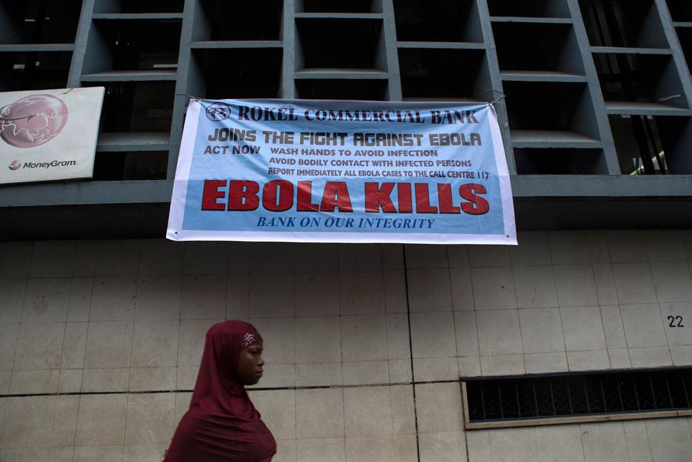 A woman passes a sign posted in an awareness campaign against the spread of Ebola in Freetown, Sierra Leone. (Pic: Reuters)