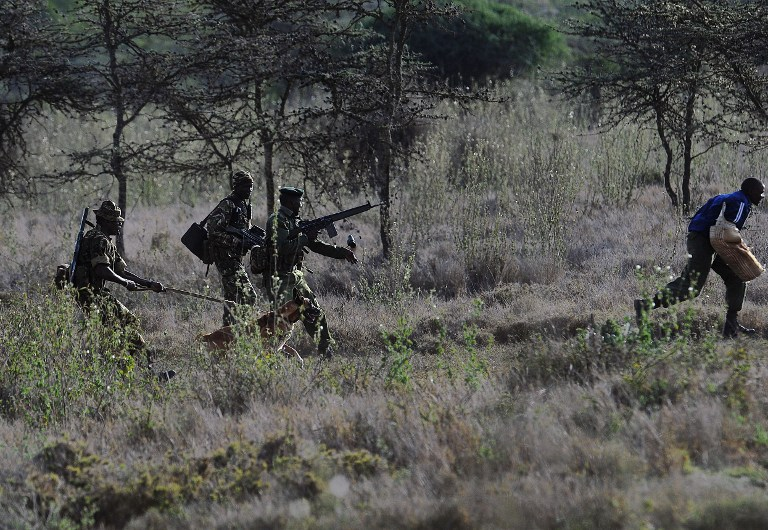 """Members of a ranger elite team run after a """"poacher"""" during a drill on August 6 2014 at the Ol Jogi rhino sanctuary. (Pic: AFP)"""