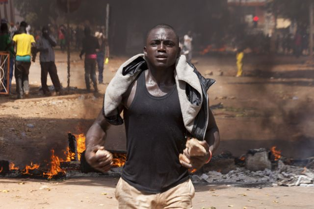 A protester carries rocks in front of a burning roadblock in Ouagadougou, capital of Burkina Faso. (Pic: AFP)
