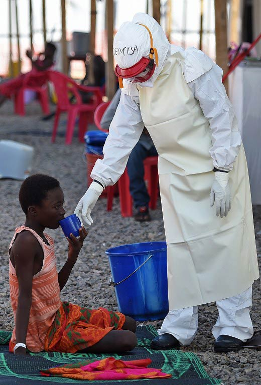 A health worker gives a drink to a young Ebola patient at the Kenama treatment centre run by the Red cross Society. (Pic: AFP)