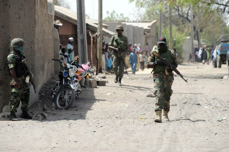 A file photo taken on April 30 2013 shows soldiers walking in the street in the remote northeast town of Baga, Borno State. Boko Haram launched renewed attacks around a captured town in restive northeast Nigeria that week, razing at least 16 towns and villages. (Pic: AFP)