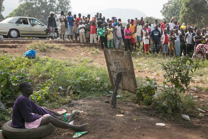 Bystanders watch as a suspected Ebola victim waits to be transported from Devils Hole North, west of Freetown. (Pic: Reuters)