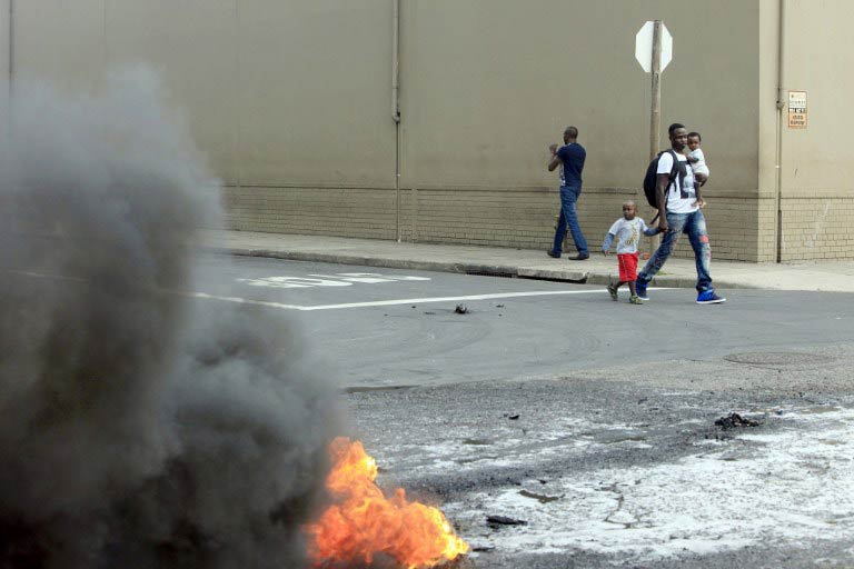 A foreign national walks with his children after clashes broke out between a group of locals and police on April 14  2015 in Durban. Hundreds of people have been displaced and forced to flee their homes this week. (Pic: AFP)