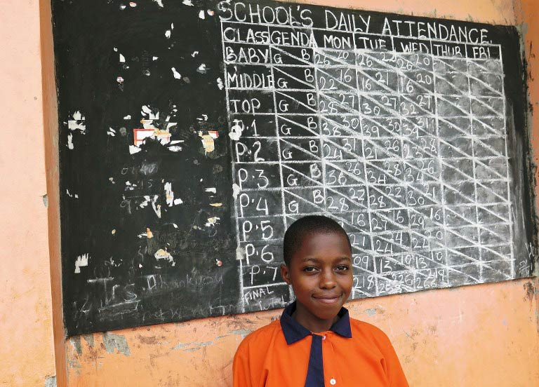 Ugandan schoolgirl Violet Nalubyayi stands in front of a black board in Lwengo on February 25 2014. (Pic: AFP)
