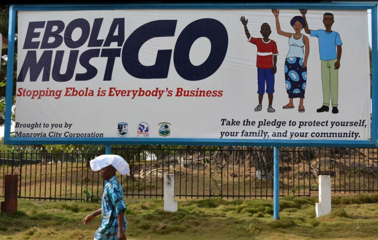 A man walks past an Ebola campaign banner in Monrovia. (Pic: AFP)