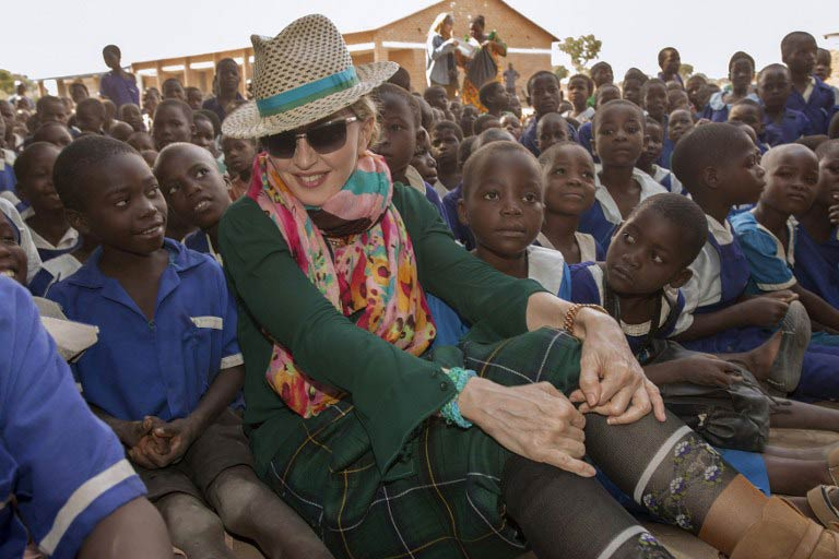US pop diva Madonna sits among Malawian children during a visit to the Mkoko Primary School, one of the schools Madonna's Raising Malawi organisation has built jointly with US organization BuildOn. (Pic: AFP)