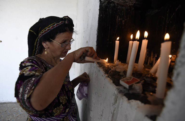 A pilgrim lights a candle inside the mosque. (Pic: AFP)
