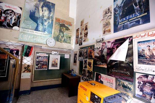 Movie posters are seen inside the Omar al-Mokhtar cinema, also known as Paradise, the only cinema still showing movies in the Libyan capital Tripoli on August 26 2015. (Pic: AFP)